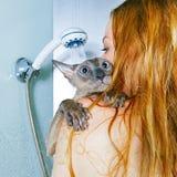 女孩和猫在阵雨 免版税库存图片