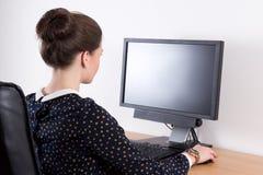 的女商人运作在办公室的后面观点 免版税库存图片