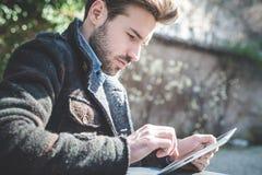 Молодая красивая фотомодель используя человека таблетки Стоковая Фотография