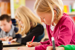 教育-学生在做家庭作业的学校 免版税库存图片