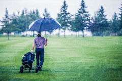 高尔夫球运动员在离开高尔夫球场的一个雨天 图库摄影