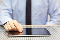 使用片剂计算机的商人在书桌上 免版税图库摄影