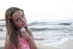 小女孩和她的老鼠玩具和海 库存图片
