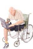 年长膝上型计算机人垂直轮椅 免版税库存照片