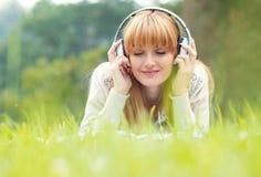 有耳机的美丽的少妇 免版税库存图片