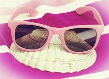 在海滩毛巾的桃红色太阳镜 图库摄影