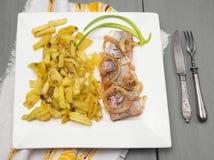 Ρέγγες με τις τηγανισμένες πατάτες στο τετραγωνικό άσπρο πιάτο Στοκ φωτογραφία με δικαίωμα ελεύθερης χρήσης