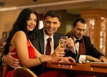 在赌博的桌后的人们 库存图片