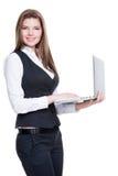 拿着膝上型计算机的成功的年轻女商人。 免版税库存照片