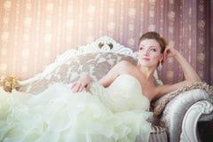 美丽的新娘坐长沙发 免版税库存照片