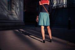 站立在街道的少妇在日落 免版税库存图片