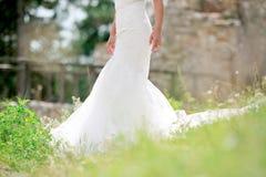 在自然室外绿草的新娘礼服 免版税图库摄影