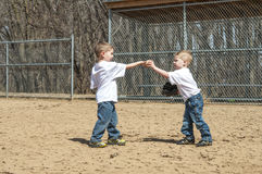 互相递棒球的男孩 免版税图库摄影