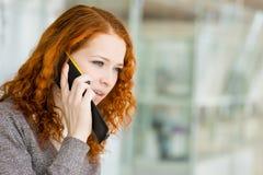 女孩讲话由电话。 免版税库存照片