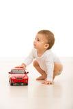 有看玩具的汽车的男孩  免版税库存图片