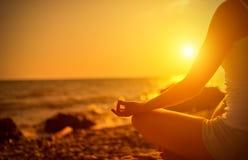 思考在瑜伽的妇女的手在海滩 库存照片