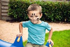 逗人喜爱的小男孩坐摇摆 免版税库存图片