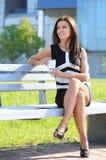 少妇饮用的咖啡在公园 库存照片