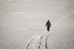 步行在雪足迹的冬天的人 免版税库存照片