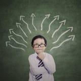 Мальчик дела думая на знаках стрелки Стоковая Фотография