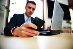 使用智能手机的商人。在智能手机的焦点。 免版税库存照片