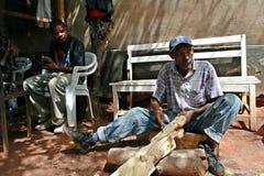 非洲黑人木雕家,运作的艺术车间 免版税图库摄影