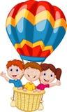 乘坐一个热空气气球的愉快的孩子动画片 图库摄影