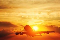 离开在日落的飞机 库存照片