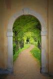 Πορεία νεράιδων μέσω της σχηματισμένης αψίδα παλαιάς πόρτας, απόκρυφη διάθεση Στοκ φωτογραφία με δικαίωμα ελεύθερης χρήσης