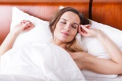 妇女在与美梦的床上 免版税库存照片