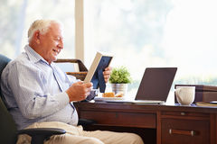 Старший человек сидя на столе смотря рамку фото Стоковые Фотографии RF