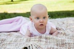 说谎在毯子的逗人喜爱的婴孩在公园 库存图片