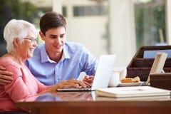 少年有膝上型计算机的孙子帮助的祖母 图库摄影