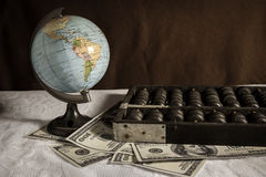 Глобус с абакусом и долларовыми банкнотами Стоковые Фото