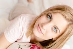 可爱的美丽的年轻白肤金发的妇女特写镜头画象有蓝眼睛和优秀皮肤在床上&看的照相机 免版税库存照片