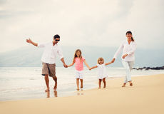 获得乐趣走在海滩的愉快的家庭在日落 免版税库存图片