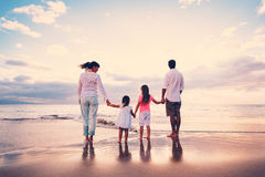 Счастливая семья имеет потеху идя на пляж на заходе солнца Стоковая Фотография