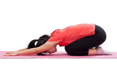 做瑜伽儿童姿势的妇女 免版税库存图片