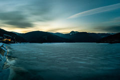 Пейзаж ночи с замороженными озером и горами под небом Стоковая Фотография