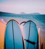在海滩的减速火箭的冲浪板 库存照片