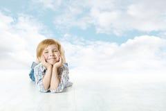 躺下微笑的孩子,小孩子蓝天 免版税库存照片