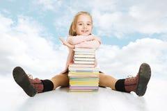 学校女孩和书架。微笑的愉快的儿童学生 免版税库存图片