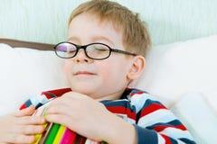 睡觉与书的小疲乏的男孩在床上 免版税库存照片