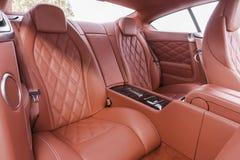 在现代豪华舒适的汽车的红色后面乘客座位 库存照片