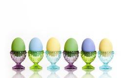 在玻璃装煮好带壳蛋之小杯的五颜六色的鸡蛋 免版税库存照片