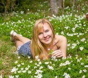 Η νέα αρκετά ξανθή γυναίκα σε ένα λιβάδι ανθίζει Στοκ φωτογραφία με δικαίωμα ελεύθερης χρήσης