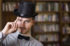 佩带高顶丝质礼帽和蝶形领结的可爱的年轻人 免版税库存图片
