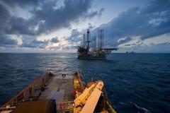 一艘近海船拖曳的抽油装置平台在日落期间 免版税库存图片