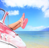 由蓝色海背景的妇女腿在汽车 免版税图库摄影