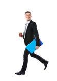 走与蓝色文件夹和咖啡的商人 免版税库存照片